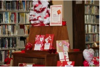 desk in a library setting exhibiting books wrapped in valentine's day paper